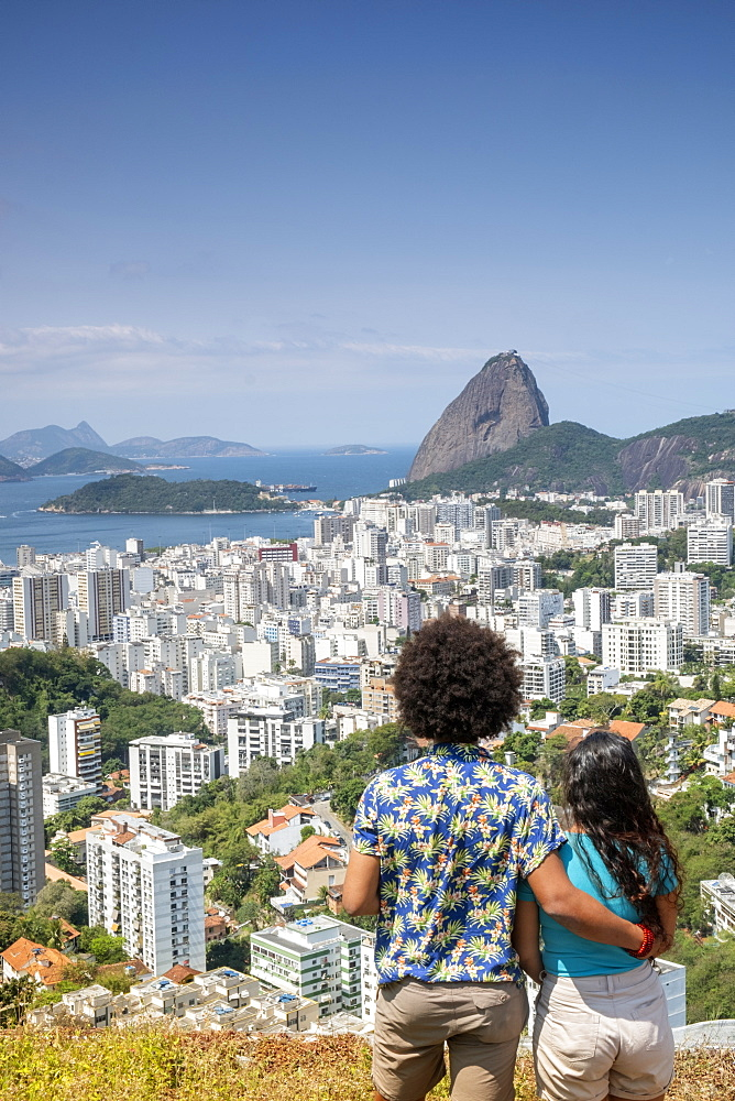 A multi-ethnic couple arm in arm looking out over Sugar Loaf mountain and the Rio skyline, Rio de Janeiro, Brazil, South America