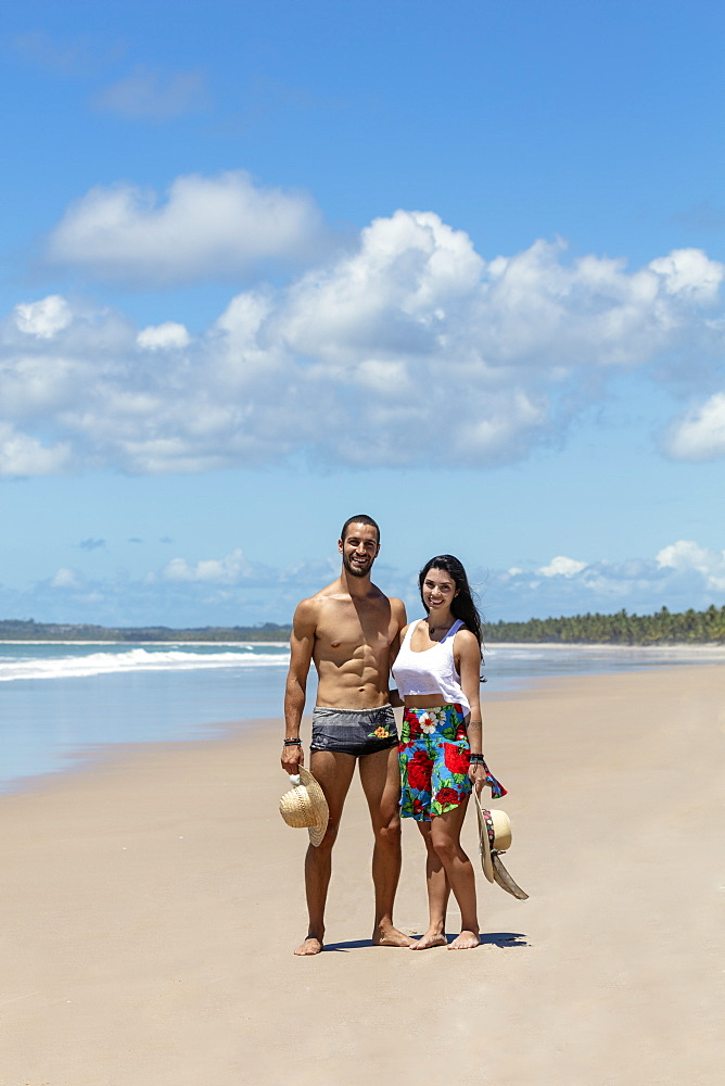 A good-looking Hispanic / Latin couple on a deserted beach smiling to camera and with copy space