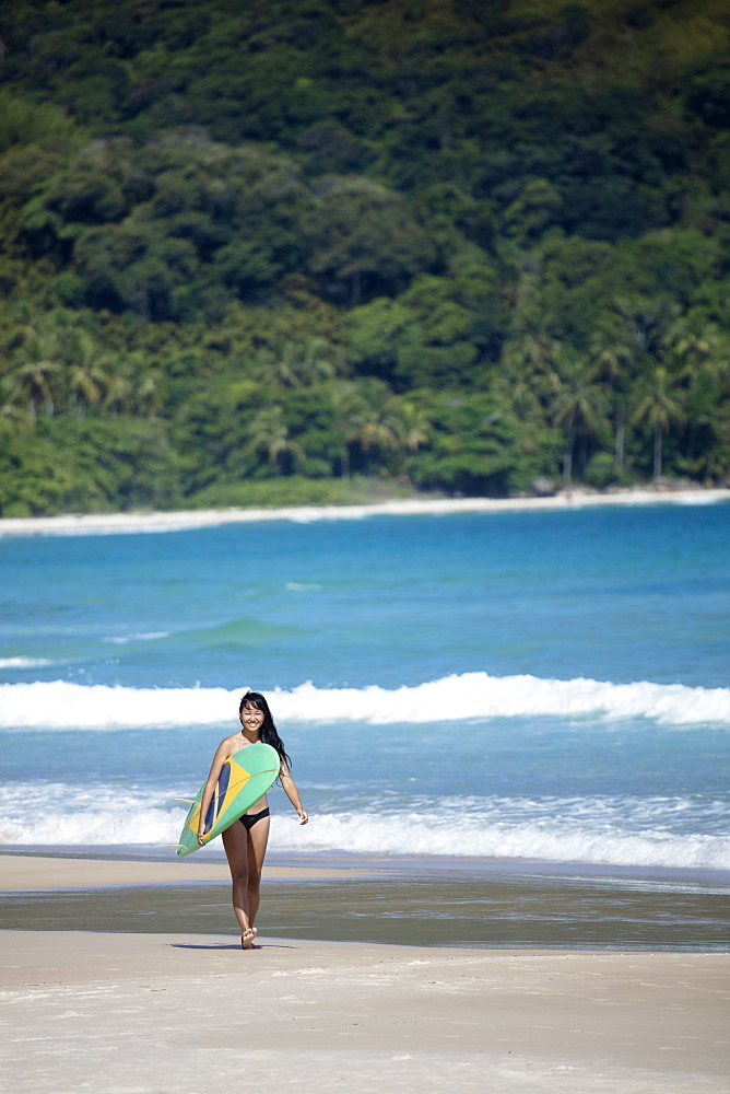 Beach shot of a Japanese Brazilian (Nipo-brasileiro) in a bikini carrying a surf board decorated with the Brazilian flag, Brazil, South America