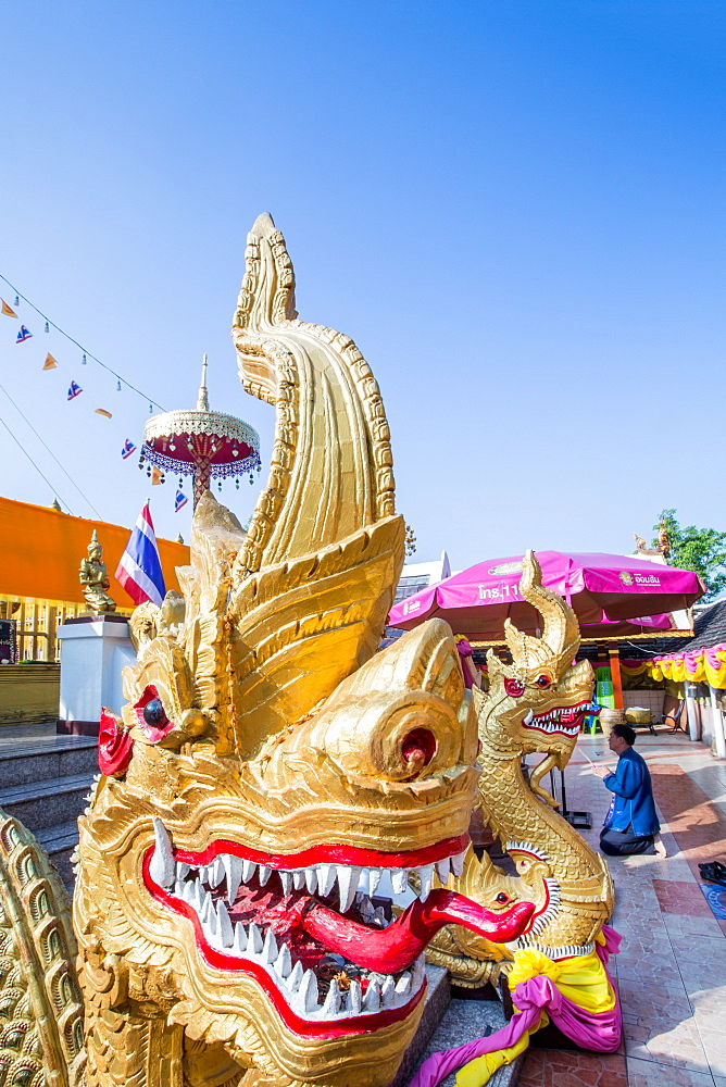 Naga head staircase and devotee at Doi Kham (Wat Phra That Doi Kham) (Temple of the Golden Mountain), Chiang Mai, Thailand, Southeast Asia, Asia