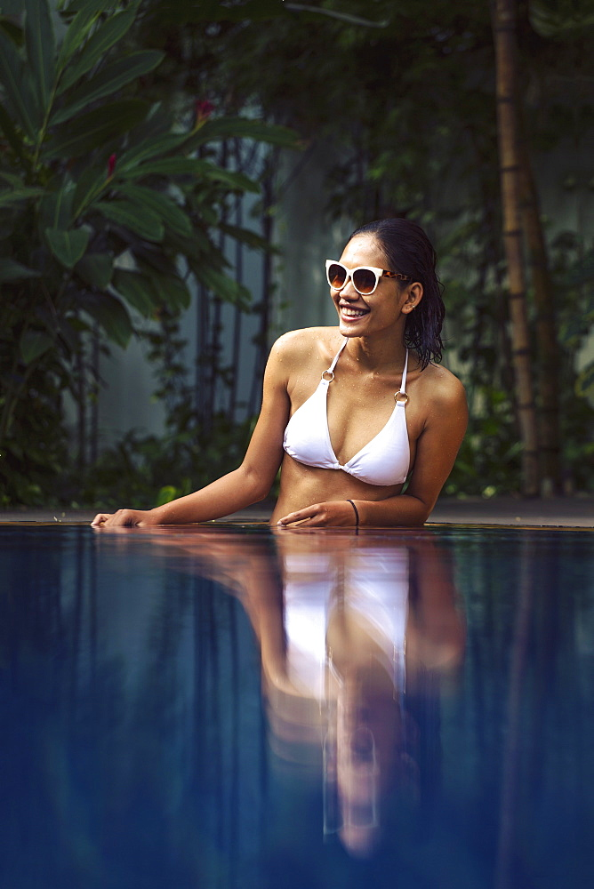 Young South East Asian woman in a white bikini in a swimming pool