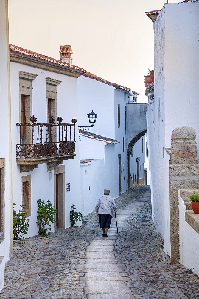 An old woman walking along an alley in the mountain village of Marvao in the Alentejo, Portugal, Europe
