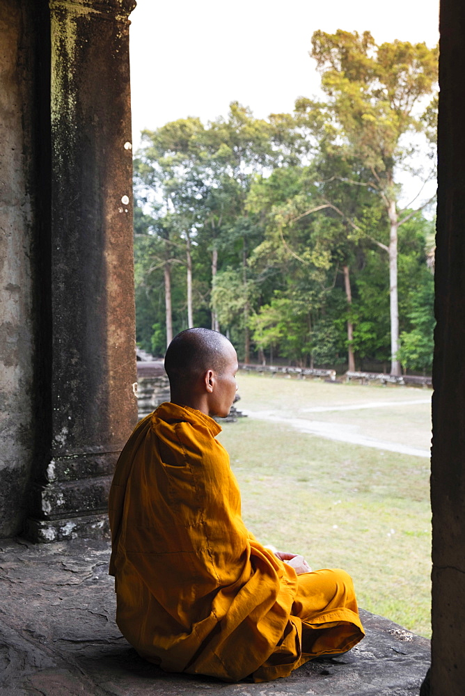 Buddhist monk sitting in a colonnaded corridor in a temple in Angkor Wat, UNESCO World Heritage Site, Siem Reap, Cambodia, Indochina, Southeast Asia, Asia - 1176-919