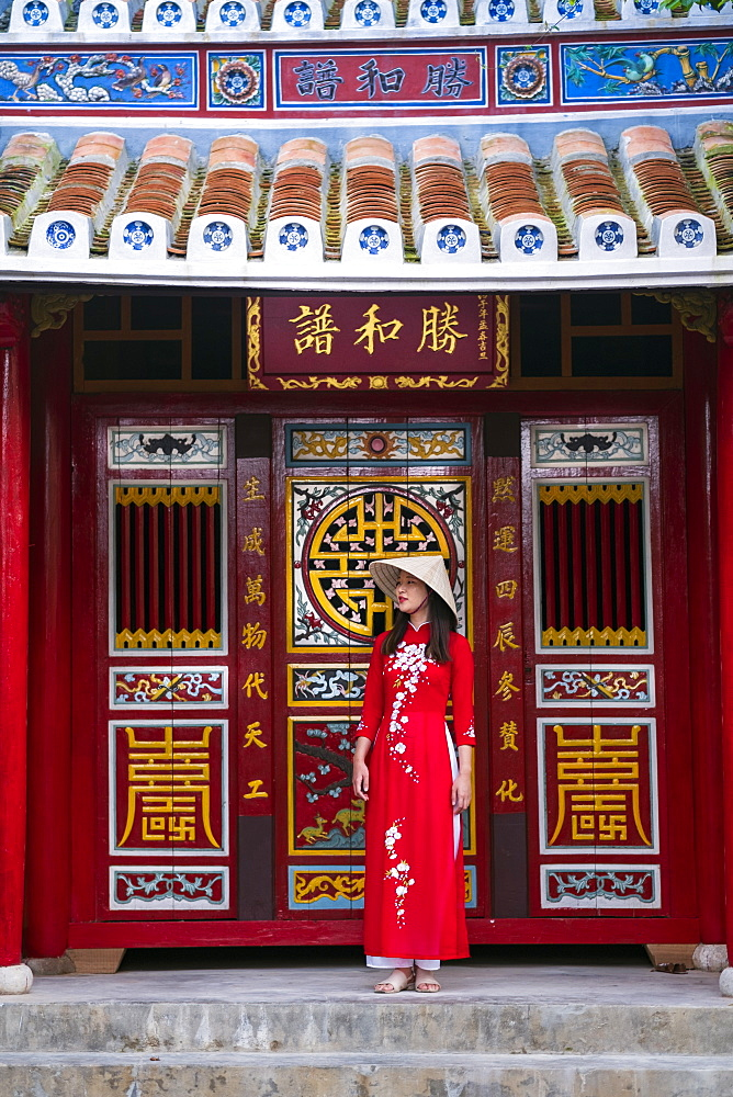 A young Vietnamese woman wearing a traditional Ao Dai dress and standing outside a temple in the historic town centre, Hoi An, Vietnam, Indochina, Southeast Asia, Asia