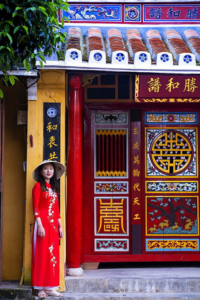 Hoi An, a young Vietnamese woman wearing a traditional Ao Dai dress and standing outside a temple in the historic town centre - 1176-966