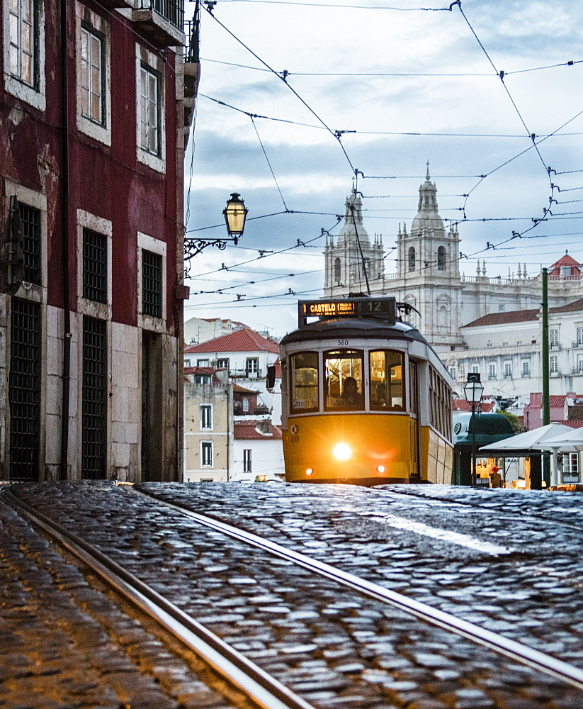 Romantic atmosphere in the old streets of Alfama with the castle in the background and tram number 28, Lisbon, Portugal, Europe