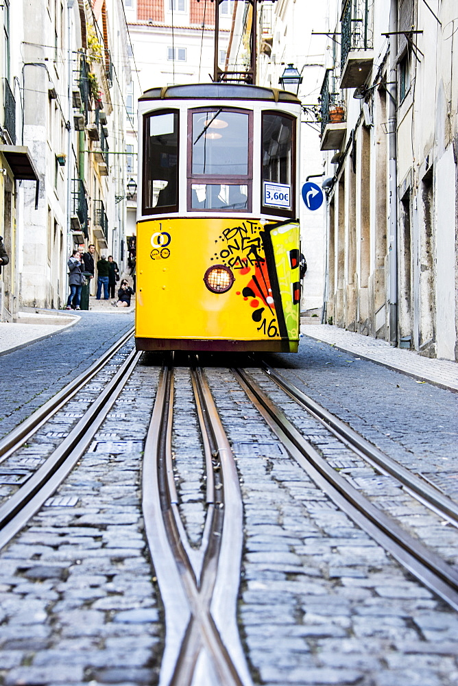 The characteristic yellow tram proceeds towards Bairro Alto, a central district of the old city of Lisbon, Portugal, Europe