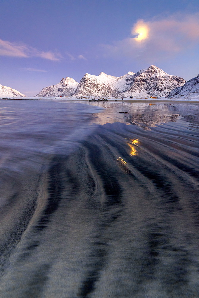 Full moon reflected in the icy sea around the surreal Skagsanden beach, Flakstad, Nordland county, Lofoten Islands, Arctic, Norway, Scandinavia, Europe