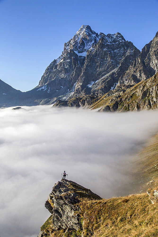 A solitary hiker admiring the profile of the Monviso (Monte Viso) emerging from the fog, Piedmont, Italy, Europe - 1179-107