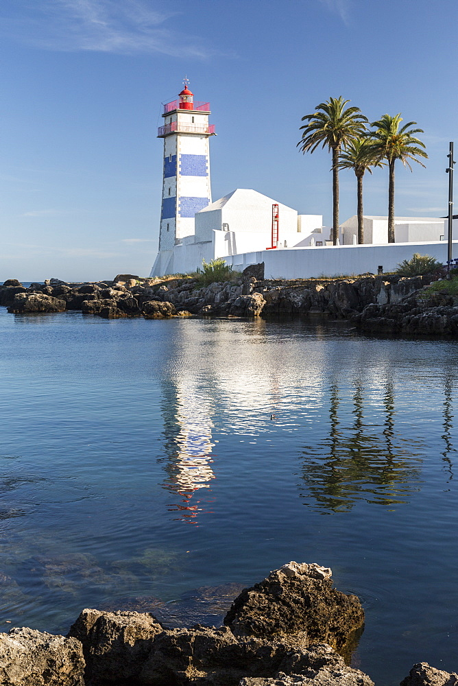 The lighthouse reflected in the blue water under the blue summer sky, Cascais, Estoril Coast, Lisbon, Portugal, Europe