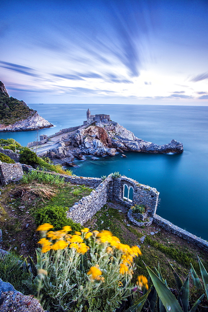 Flowers and blue sea frame the old castle and church at dusk, Portovenere, UNESCO World Heritage Site, La Spezia Province, Liguria, Italy, Europe