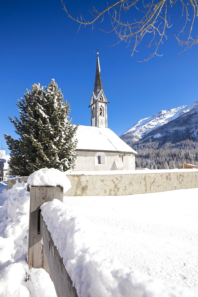 Alpine church covered with snow framed by blue sky, Cinuos, Canton of Graubunden, Engadine, Switzerland, Europe - 1179-1903