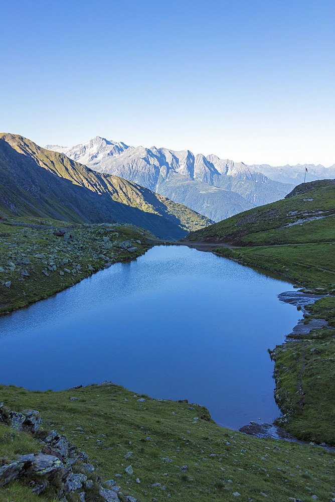 The alpine lake frames the green valley and Rifugio Bozzi Val Di Viso Camonica Valley province of Brescia Lombardy Italy Europe