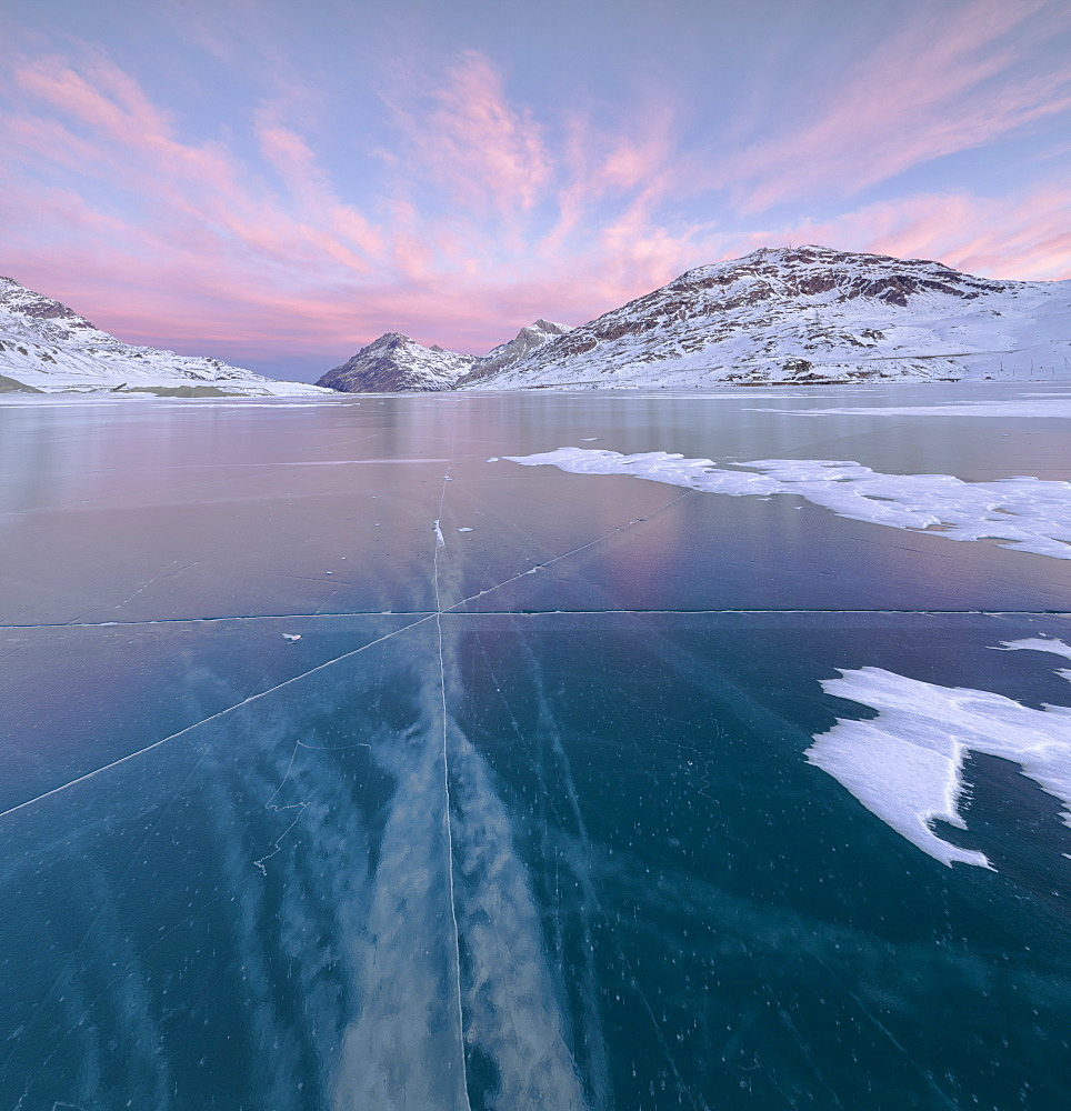Panorama of the frozen Lago Bianco framed by pink clouds at dawn, Bernina Pass, canton of Graubunden, Engadine, Switzerland, Europe