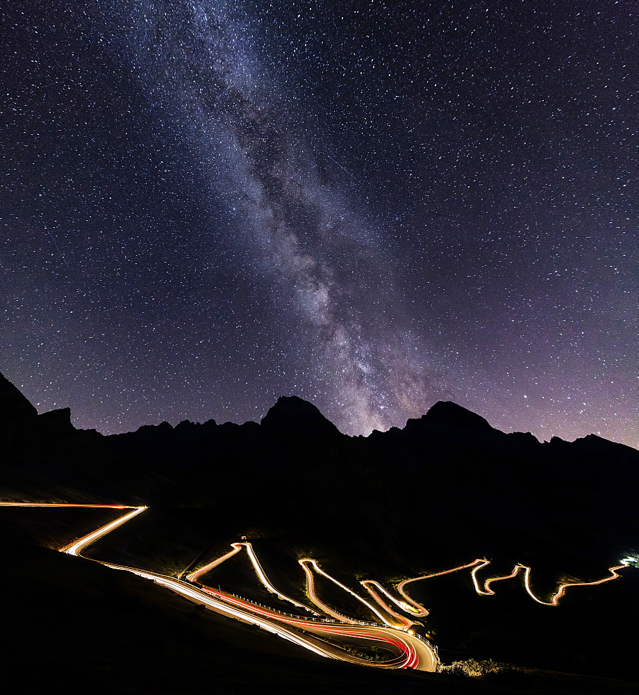 Panorama of the Milky Way and lights of car trace at Stelvio Pass, Valtellina, Lombardy, Trentino Alto Adige, Italy, Europe
