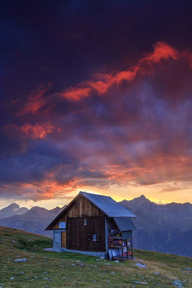 Wooden hut framed by fiery sky and clouds at sunset Muottas Muragl St.Moritz Engadine Canton of Graubünden Switzerland Europe - 1179-2087