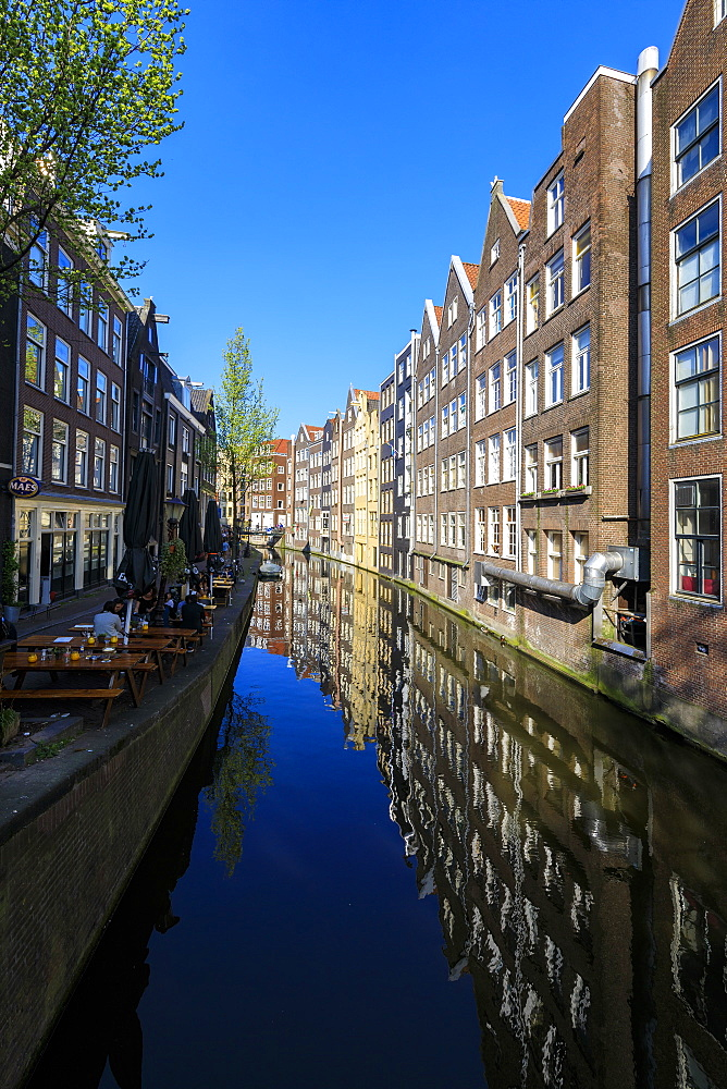 Typical houses reflected in the blue water of a canal, Amsterdam, Holland (The Netherlands), Europe