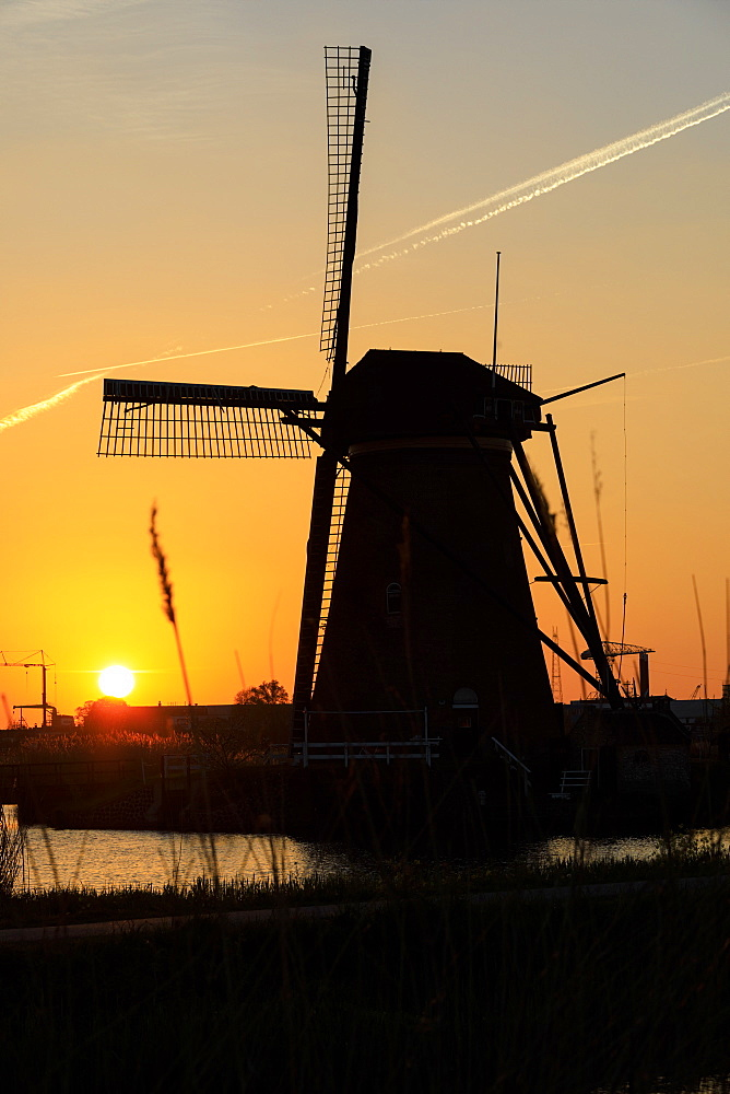 Silhouette of typical windmill framed by the fiery sky at sunset, Kinderdijk, UNESCO World Heritage Site, Molenwaard, South Holland, The Netherlands, Europe