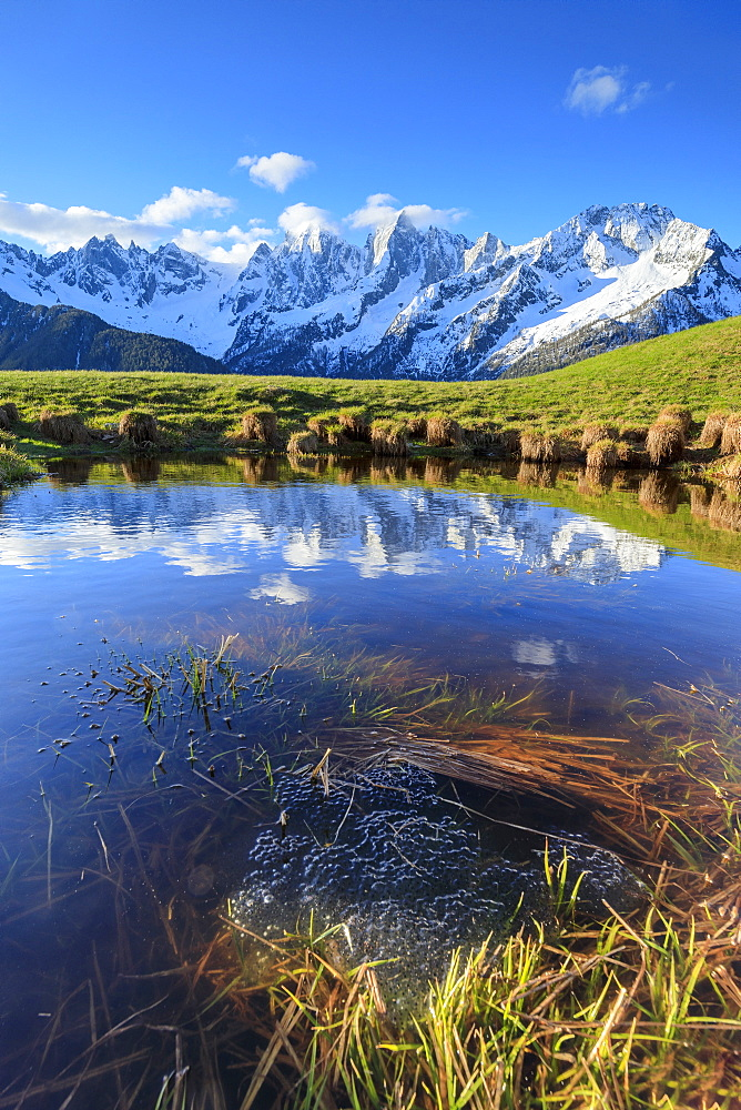 Snowy peaks and blue sky reflected in water at dawn Tombal Soglio Bregaglia Valley canton of Graubünden Switzerland Europe
