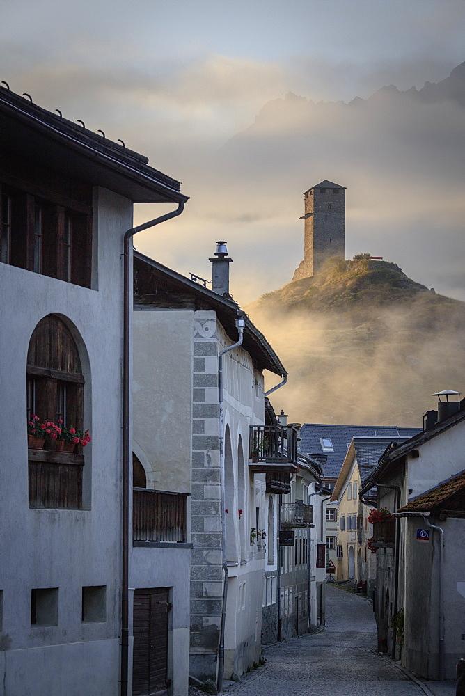 Misty sky on the alpine village of Ardez at sunrise, canton of Graubünden, district of Inn, lower Engadine, Switzerland, Europe