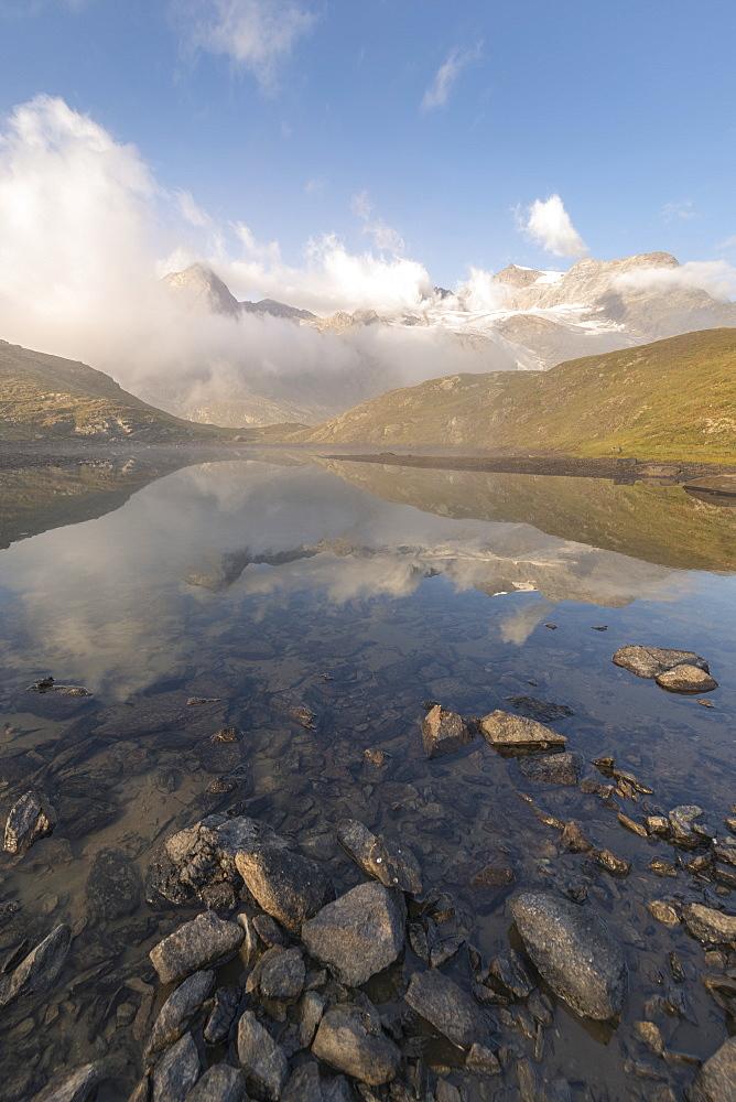 Peaks of mountain range reflected in alpine lake, Bernina Pass, Poschiavo Valley, canton of Graubünden, Engadine, Switzerland