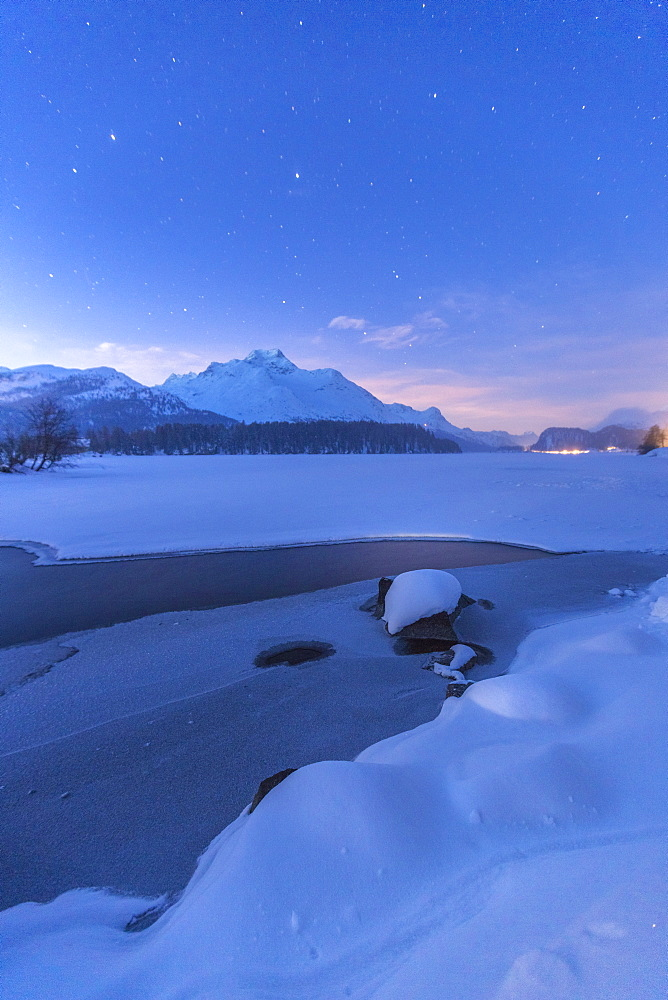 Stars above Piz Da La Margna and icy Lake Sils, Maloja, Engadine, Canton of Graubunden, Switzerland, Europe