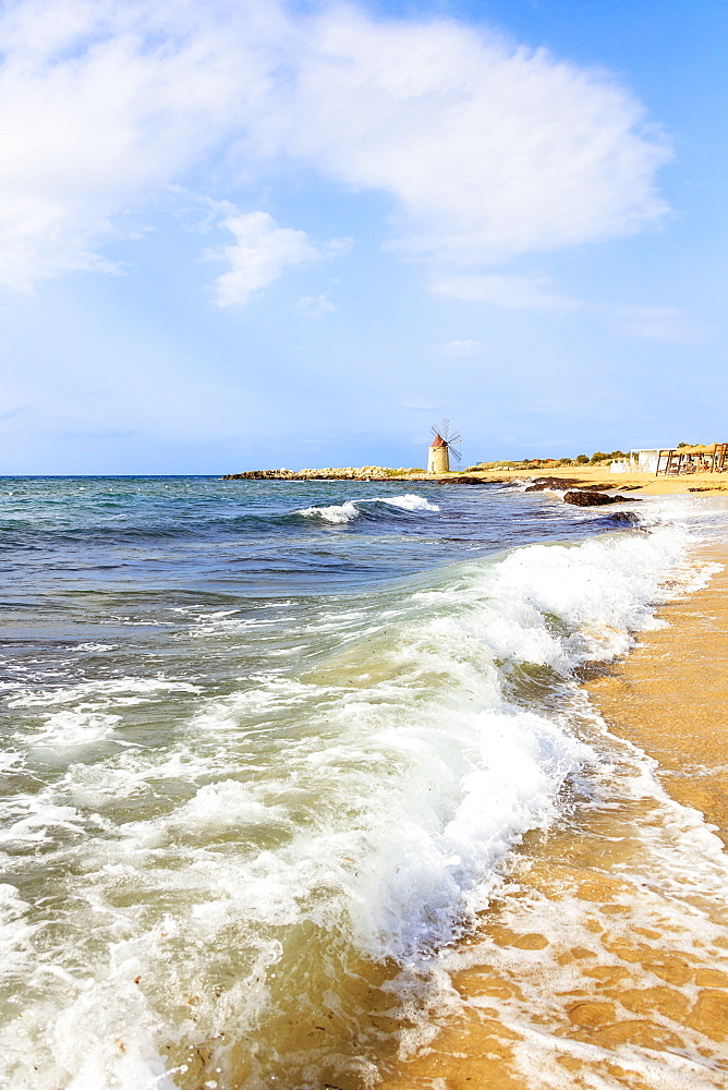 Sea waves crashing on sand beach of Baia dei Mulini, Trapani, Sicily, Italy