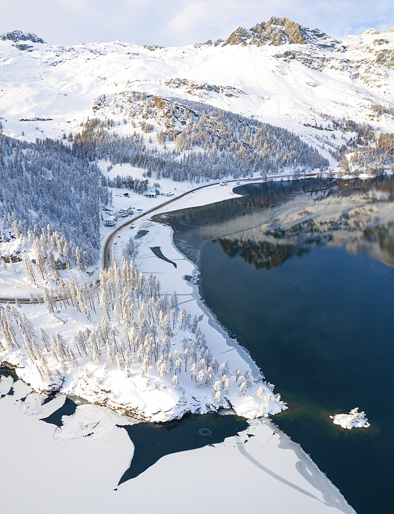 Aerial panoramic view of road around frozen Lake Sils, Plaun da Lej, Maloja Region, Canton of Graubunden, Engadine, Switzerland, Europe
