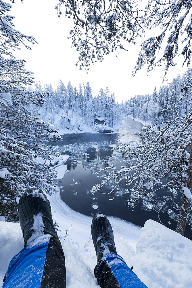 Hiker rests on the snow above Myllykoski rapids, Juuma, Oulanka National Park, Kuusamo, Lapland, Finland