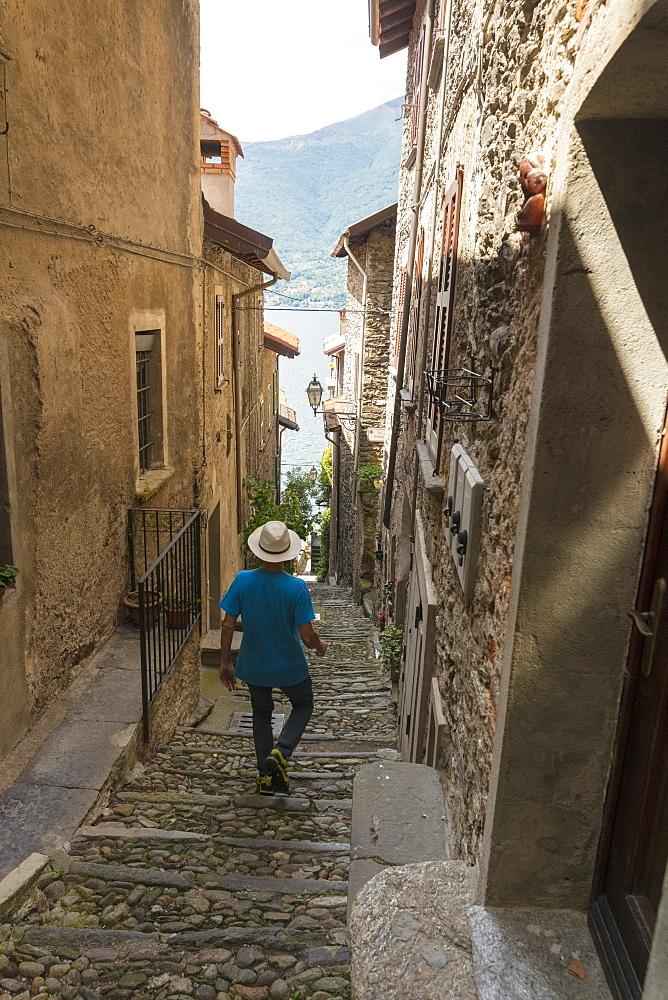 Man walks down old alley, Corenno Plinio, Dervio, Lake Como, Lecco province, Lombardy, Italy, Europe