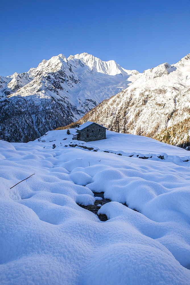 Stone hut at the foot of the snowy Monte Vazzeda, Alpe dell'Oro, Valmalenco, Valtellina, Sondrio province, Lombardy, Italy, Europe