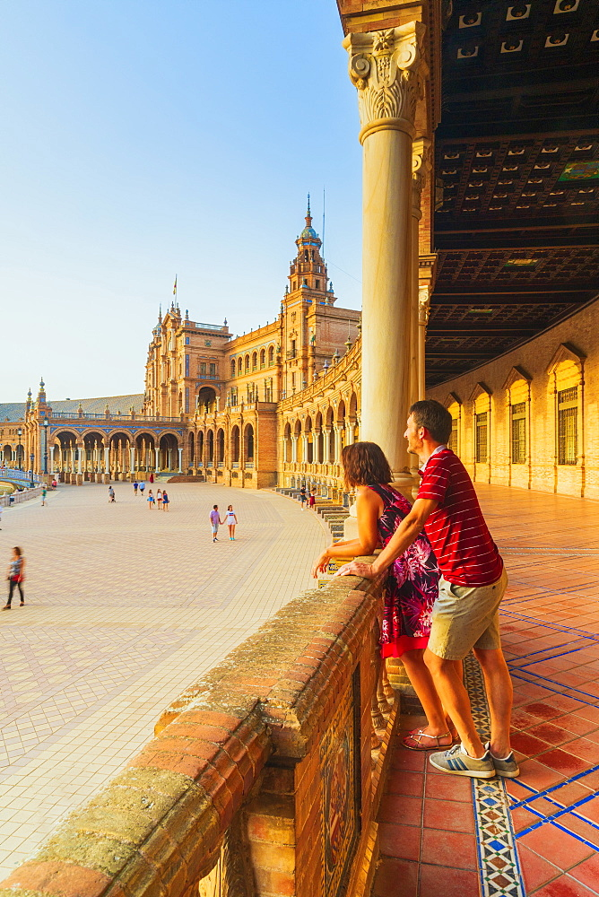 Couple of tourists admire the square from the decorated portico, Plaza de Espana, Seville, Andalusia,Spain, Europe
