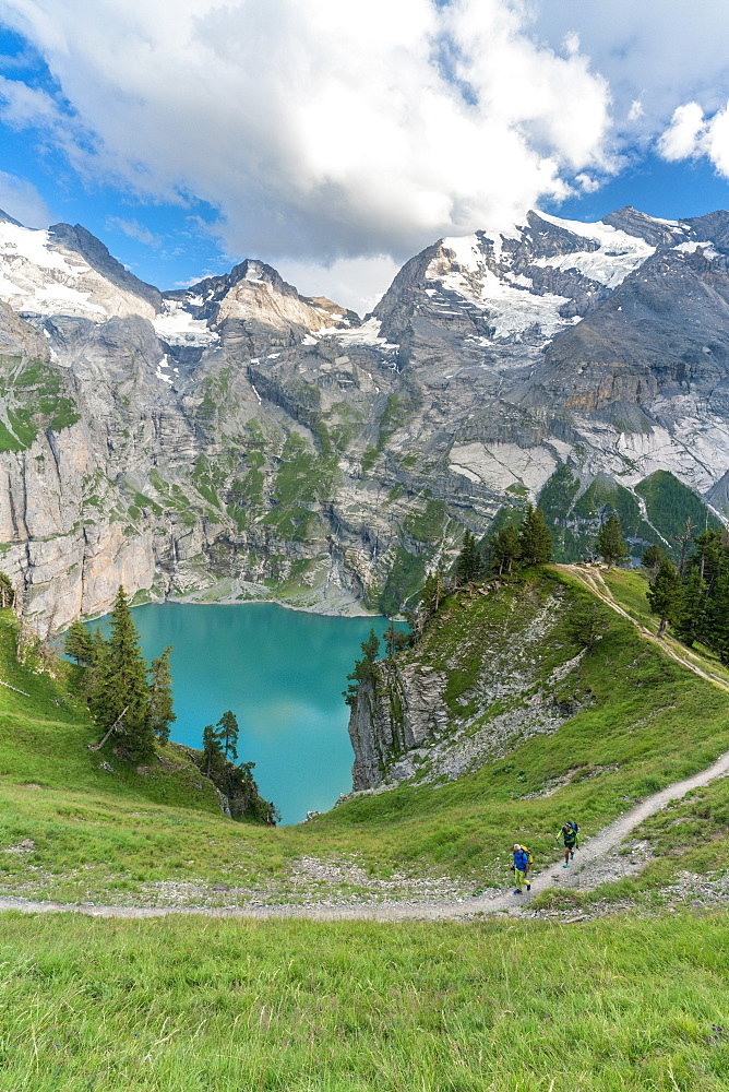 High angle view of two hikers walking on path above Oeschinensee lake, Bernese Oberland, Kandersteg, Canton of Bern, Switzerland, Europe