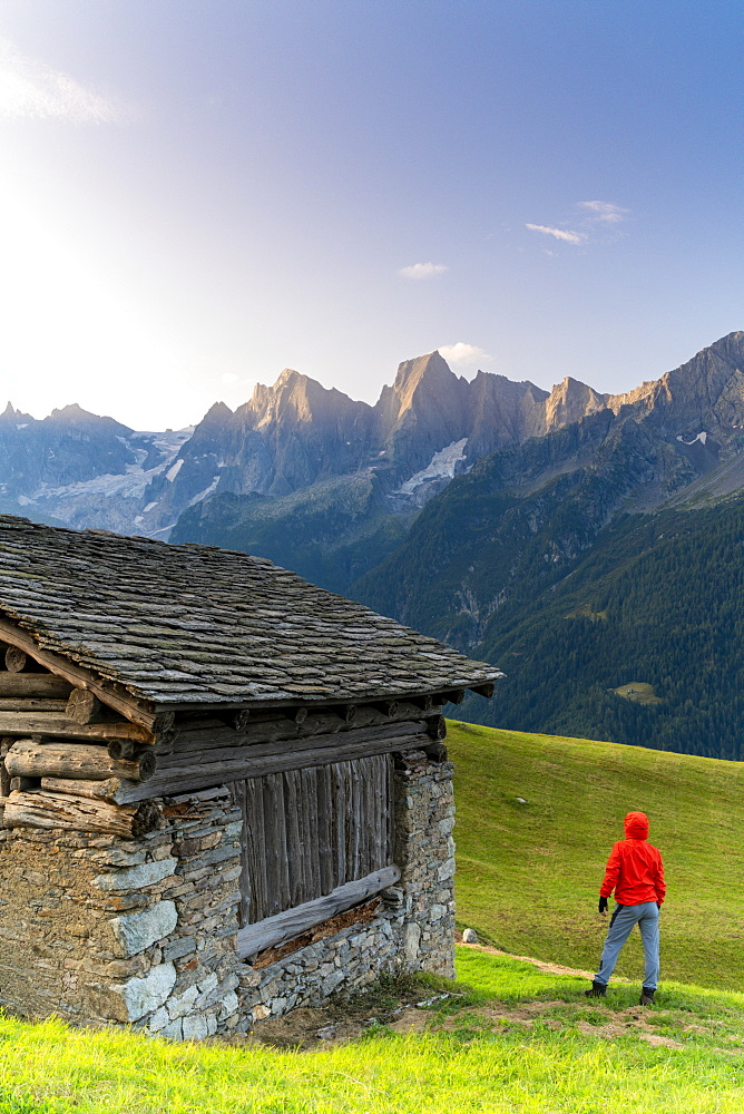 Rear view of man out of a stone hut looking at Piz Cengalo and Badile, Tombal, Val Bregaglia, canton of Graubunden, Switzerland, Europe