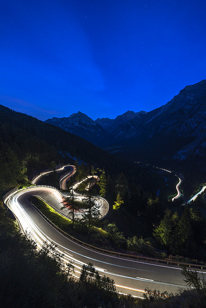 Light trails on the hairpin curves of Maloja Pass mountain road at night, Engadine, Canton of Graubunden, Switzerland, Europe - 1179-4076