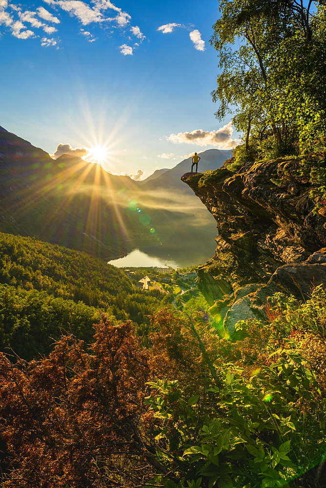 Rear view of man on top of rocks admiring Geiranger at sunset, Stranda municipality, Sunnmore, More og Romsdal county, Norway, Scandinavia, Europe - 1179-4096