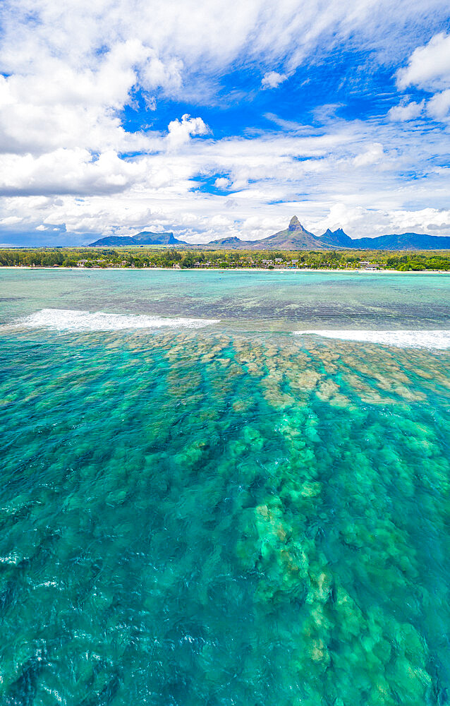 Aerial panoramic of coral reef and Piton de la Petite Riviere Noire mount surrounding Flic en Flac beach, Black River, Mauritius