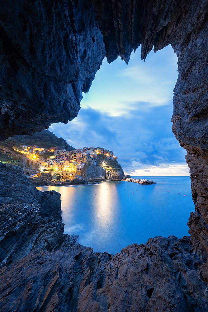 Dusk lights over Manarola seen from a sea cave, Cinque Terre, UNESCO World Heritage Site, La Spezia province, Liguria, Italy, Europe