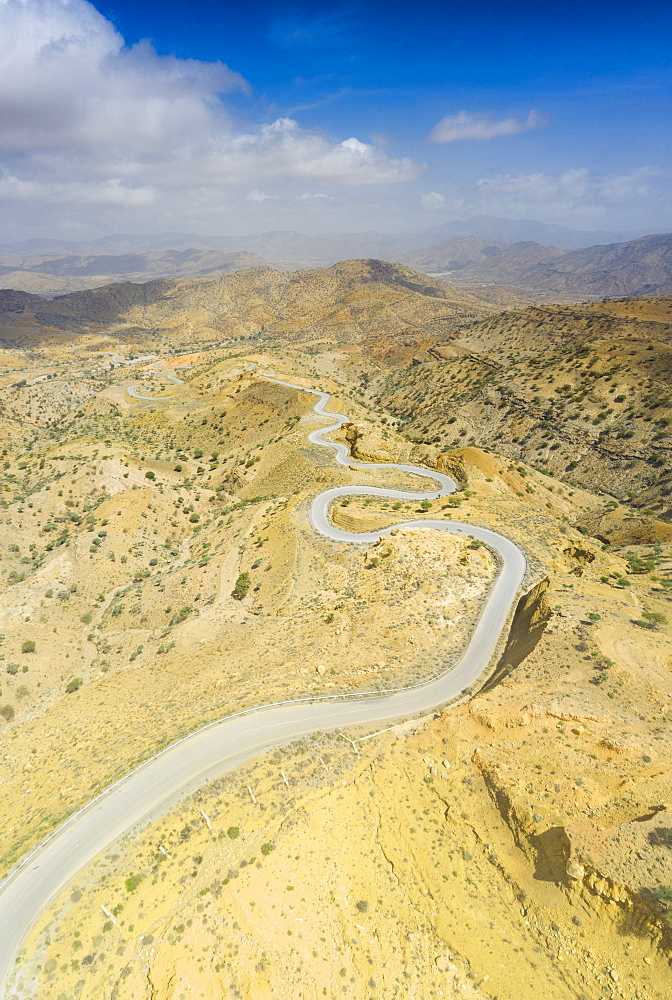 Panoramic of winding road towards Berhale crossing the dry landscape of Danakil desert, Afar Region, Ethiopia, Africa (drone)