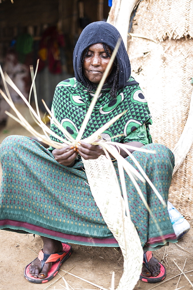Elderly woman working with straw in Melabday village, Asso Bhole, Dallol, Danakil Depression, Afar Region, Ethiopia, Africa