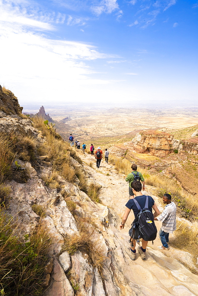 Hikers ventures on rock path towards the rock-hewn churches of Gheralta Mountains, Tigray Region, Ethiopia, Africa