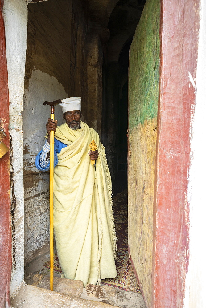 Orthodox priest holding the hand cross at the entrance of Maryam Korkor church, Gheralta Mountains, Tigray Region, Ethiopia, Africa