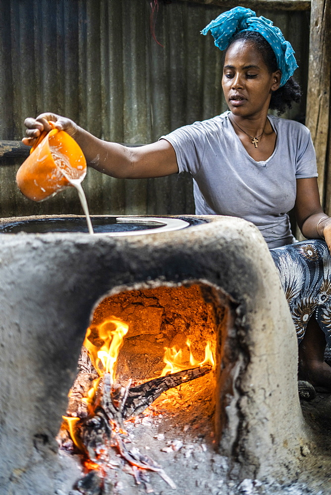 Woman making injera bread on traditional oven, Berhale, Afar Region, Ethiopia, Africa