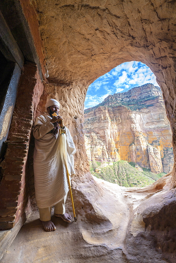 Ethiopian Orthodox priest holding the hand cross at entrance of Abuna Yemata Guh church, Gheralta Mountains, Tigray, Ethiopia, Africa