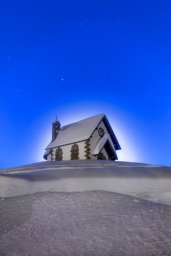 Stars over the church of Madonna Assunta in winter, Rolle Pass, Pale di San Martino, Dolomites, Trentino-Alto Adige, Italy