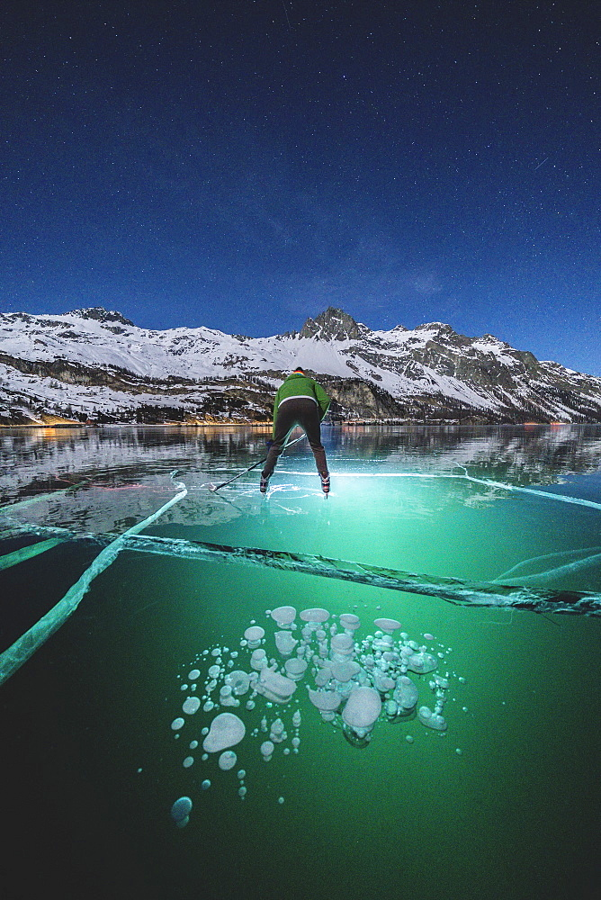 Man skating on frozen Lake Sils lit by head torch at night, canton of Graubunden, Engadine, Switzerland