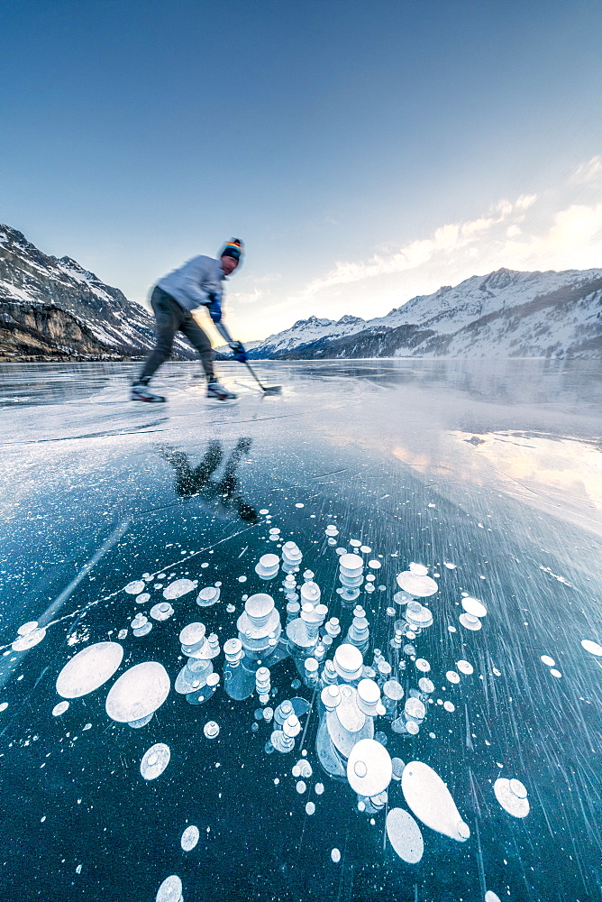 Man playing ice hockey on frozen Lake Sils, Engadine, canton of Graubunden, Switzerland, Europe