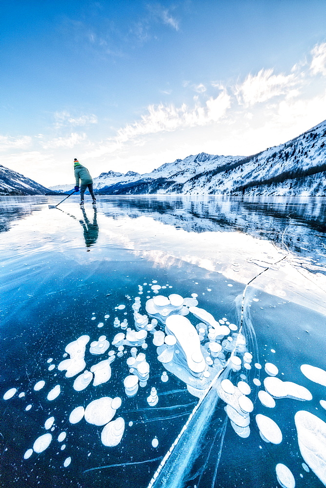 Man playing ice hockey on frozen Lake Sils covered of bubbles, Engadine, canton of Graubunden, Switzerland, Europe
