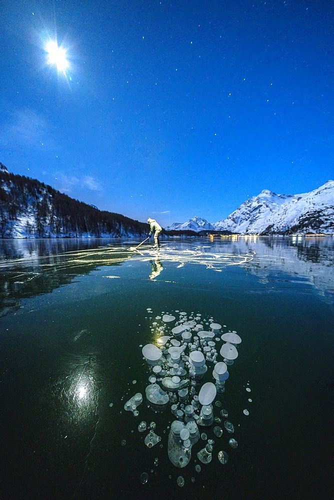 Full moon on ice skater on frozen Lake Sils lit by head torch, Engadine, canton of Graubunden, Switzerland, Europe