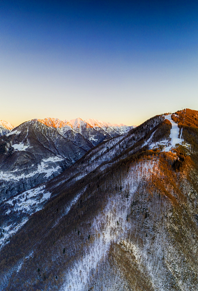 Aerial view by drone of ski slopes of Pian Delle Betulle and Alpe Paglio lit by sunset, Valsassina, Lecco province, Lombardy, Italy, Europe